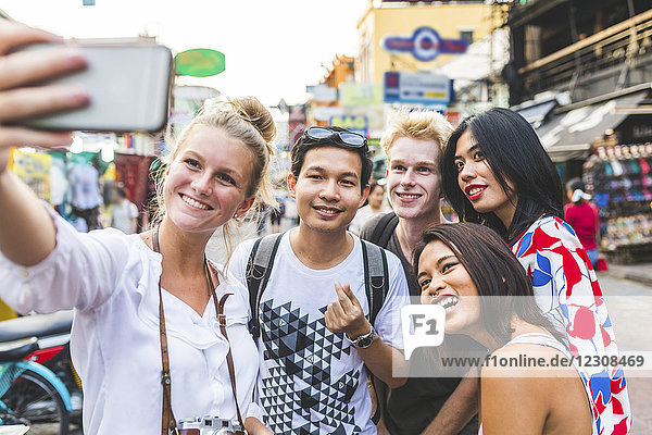 Thailand  Bangkok  Khao San Road  Gruppe von Freunden  die Selfie mit Smartphone nehmen