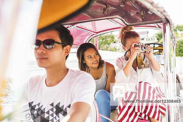 Thailand,  Bangkok,  Freunde auf Tuk Tuk Tuk fotografieren mit einer alten Kamera