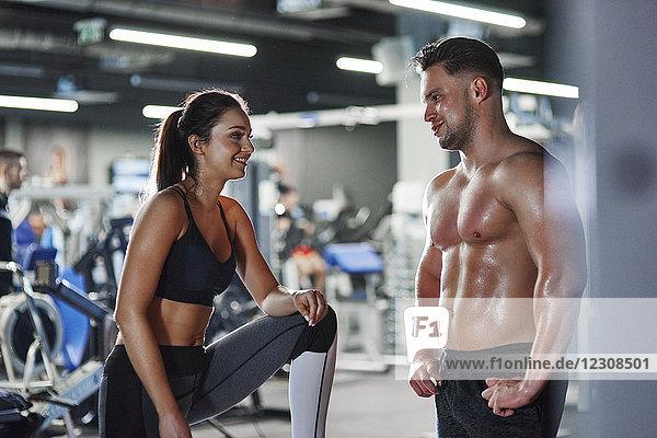 Lächelnder Mann und Frau reden im Fitnessstudio