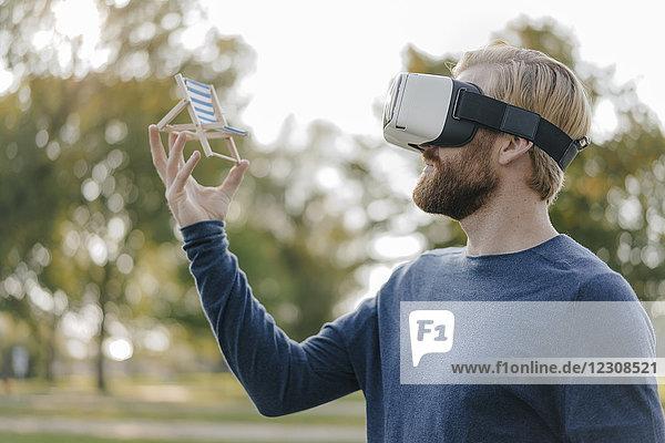 Mann im herbstlichen Park mit Virtual Reality Brille auf Mini-Strandliege
