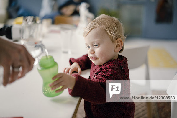 Baby boy with drinking bottle