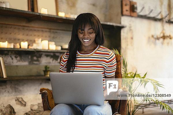 Porträt einer lächelnden jungen Frau auf einem Ledersessel mit Laptop