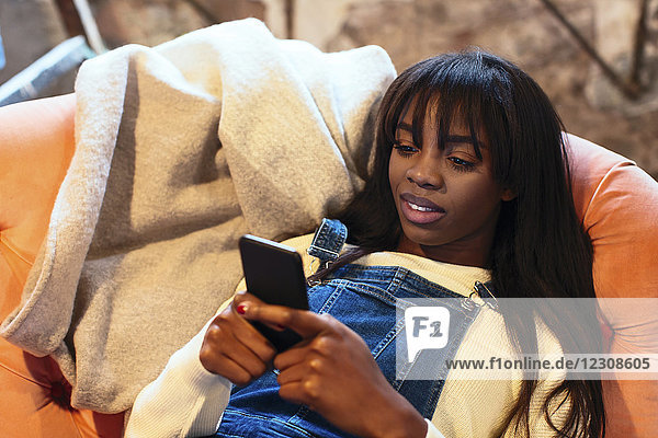Porträt einer lächelnden jungen Frau  die mit dem Handy auf der Couch liegt.