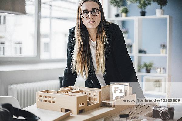 Portrait des Architekten mit Architekturmodell im Büro