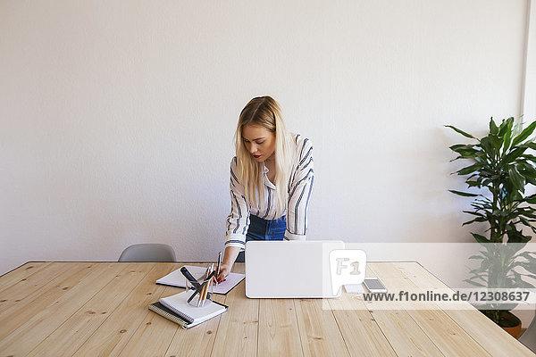 Junge Geschäftsfrau am Schreibtisch stehend  mit Laptop