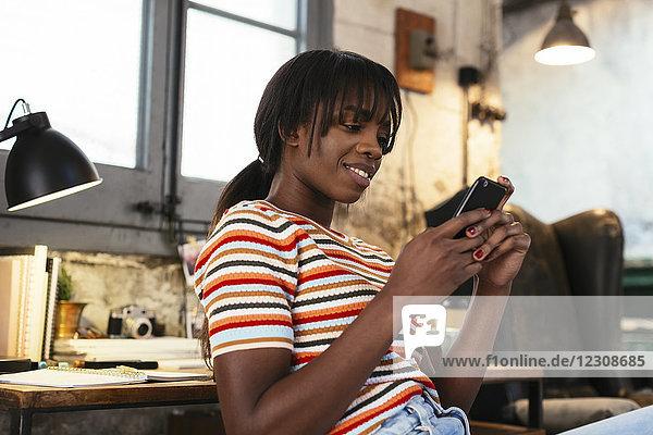 Porträt einer lächelnden jungen Frau  die mit dem Handy in einem Loft sitzt.