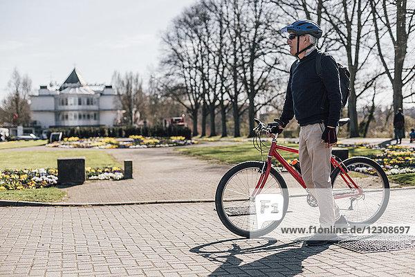 Senior mit Fahrrad im Park