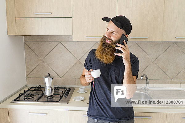 Portrait of bearded man on the phone standing in kitchen with espresso cup