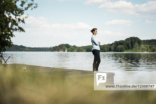 Frau steht auf einem Steg am See