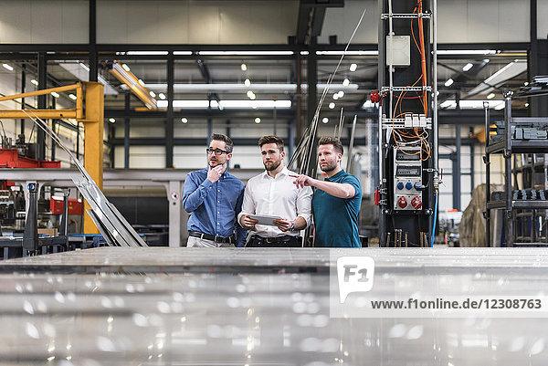 Drei Männer teilen sich die Tablette in der Fabrikhalle.
