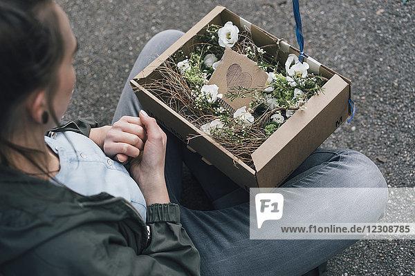 Frau mit Blumenarrangement im Karton auf dem Boden sitzend
