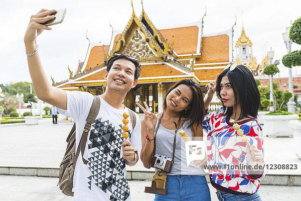 Thailand  Bangkok  drei Freunde mit Straßenessen  die Selfie nehmen
