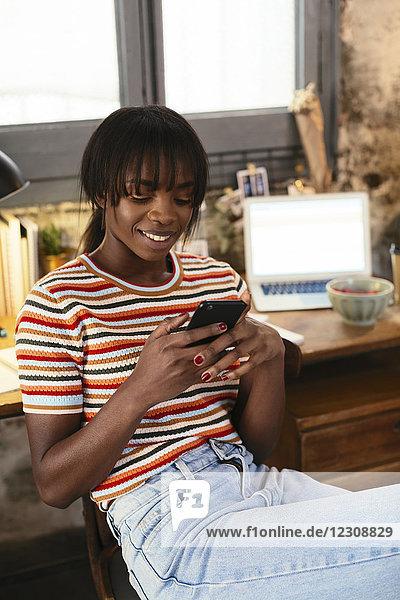 Porträt einer lächelnden jungen Frau  die mit dem Handy vor dem Schreibtisch in einem Loft sitzt.