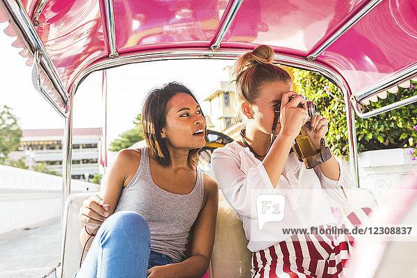 Thailand,  Bangkok,  zwei Freunde auf Tuk Tuk Tuk beim Fotografieren mit einer alten Kamera
