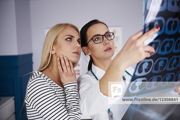 Arzt zeigt der jungen Frau das Röntgenbild