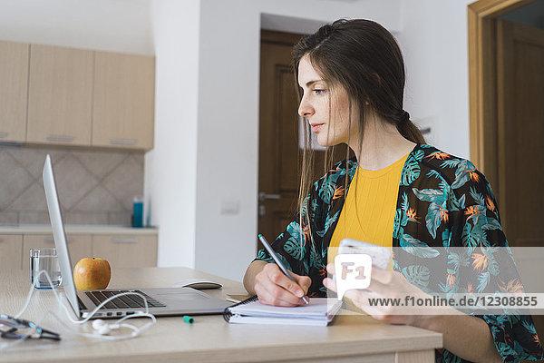 Junge Frau sitzt zu Hause am Tisch mit Handy und Laptop und macht sich Notizen.