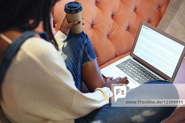 Junge Frau sitzt auf der Couch mit Kaffee zu gehen mit Laptop