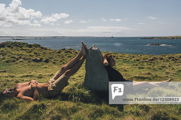Frankreich  Bretagne  Landeda  Dunes de Sainte-Marguerite  junges Paar entspannt im Gras an der Küste