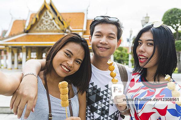 Thailand,  Bangkok,  Porträt von Freunden mit Straßenessen und Selbstbedienung
