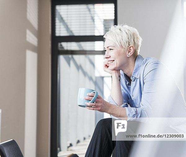 Lächelnde Frau mit Tasse Kaffee im Büro auf dem Tisch sitzend