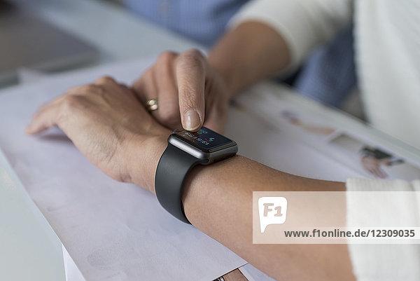 Woman's hand adjusting smartwatch at desk