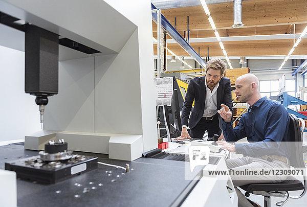 Zwei Männer reden an der Maschine in der modernen Fabrik