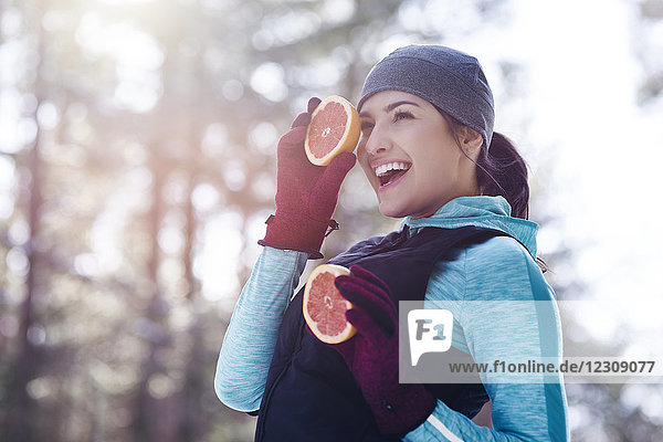 Portrait of laughing young woman wearing sportswear holding two halves of grapefruit