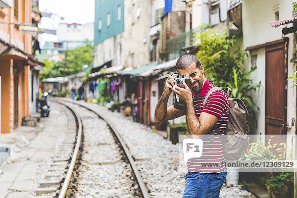 Vietnam  Hanoi  Mann in der Stadt beim Fotografieren mit einer altmodischen Kamera