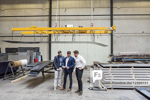 Drei Männer stehen in der Fabrikhalle und schauen auf die Tablette.