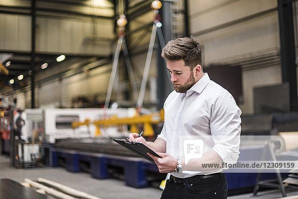 Mann schreibt auf Klemmbrett in der Fabrikhalle