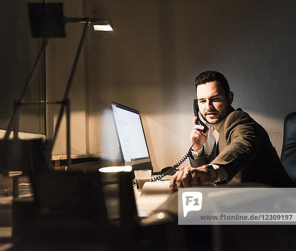Geschäftsmann am Telefon im Büro bei Nacht
