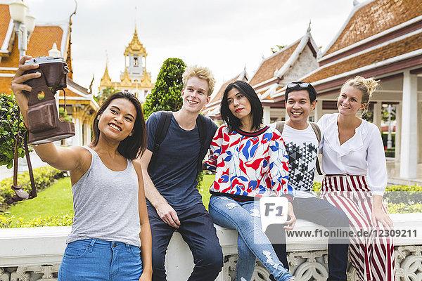 Thailand,  Bangkok,  fünf Freunde,  die Selfie mit Smartphone vor dem Tempelkomplex nehmen