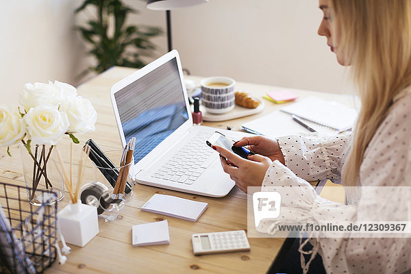 Blonde Geschäftsfrau am Schreibtisch sitzend  arbeitend
