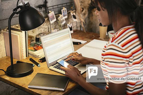 Frau sitzt am Schreibtisch mit Smartphone und Laptop
