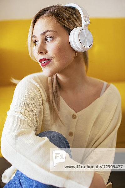 Blonde Frau mit Kopfhörer über Smartphone zu Hause