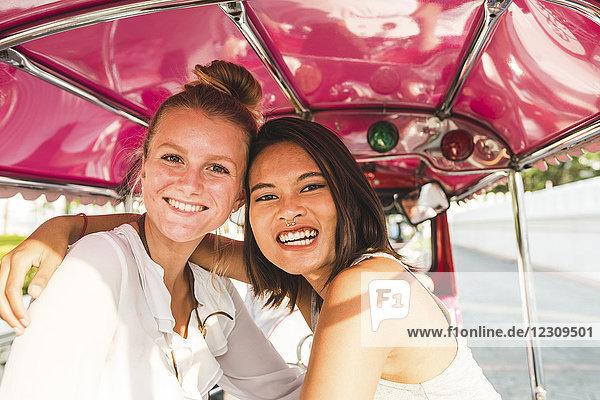 Thailand  Bangkok  Portrait von zwei glücklichen Freunden auf Tuk Tuk Tuk