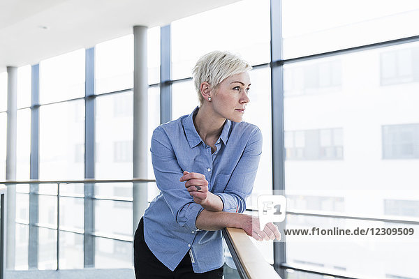Woman in office building leaning on railing