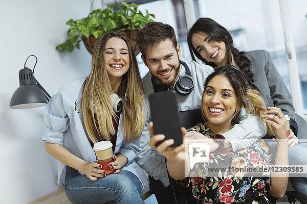 Fröhliche Gelegenheitsmitarbeiter im Büro  die einen Selfie nehmen