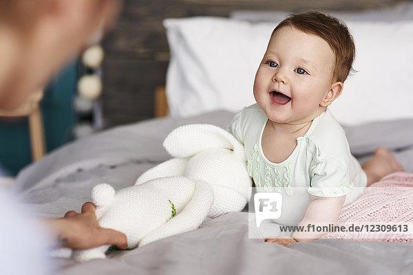 Glückliches Baby mit Kuscheltier auf dem Bett zu Hause mit Blick auf ihre Mutter
