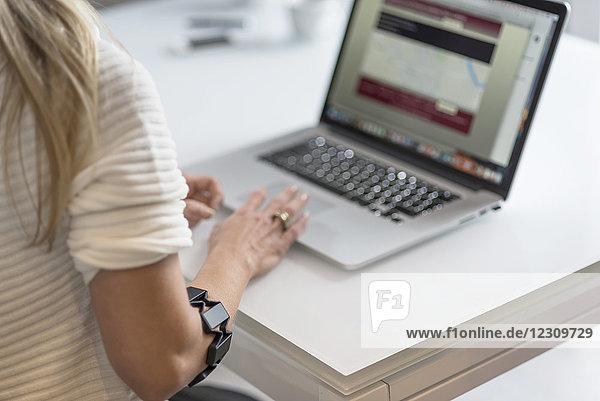 Frau mit tragbarem Arm mit Laptop am Schreibtisch