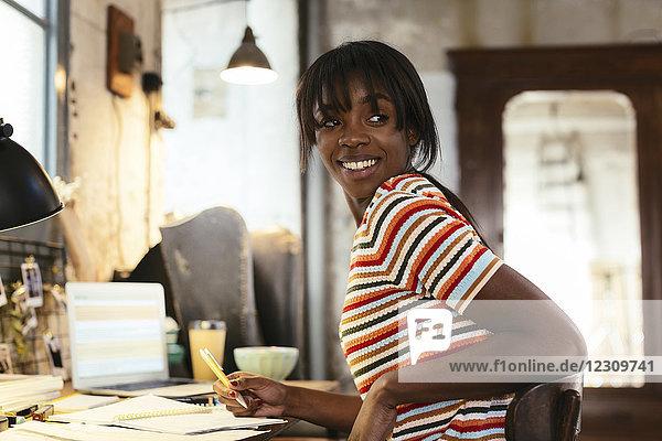 Porträt einer lächelnden jungen Frau  die am Schreibtisch in einem Loft sitzt.