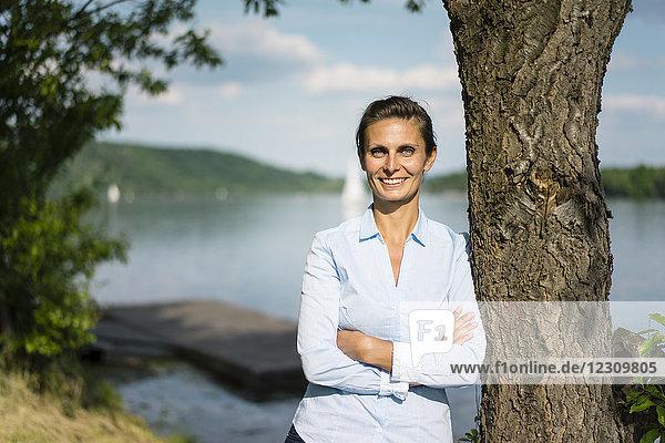 Porträt einer lächelnden Frau  die sich an einen Baum an einem See lehnt.