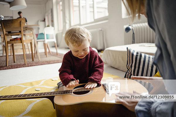 Kleiner Junge erkundet mit seiner Mutter eine Gitarre