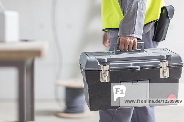 Close-up of construction worker carrying tool box
