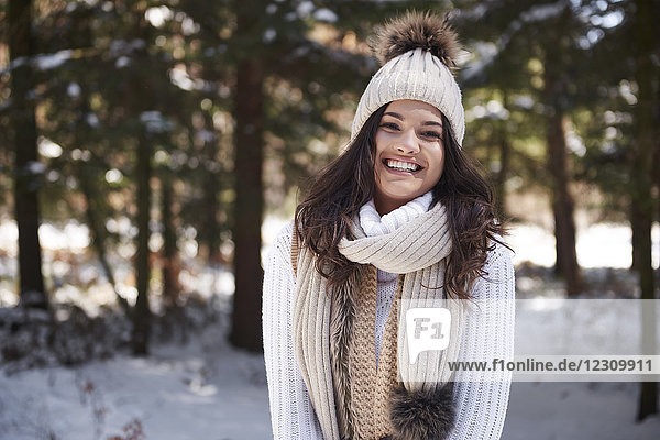 Portrait of laughing young woman wearing knitwear in winter forest