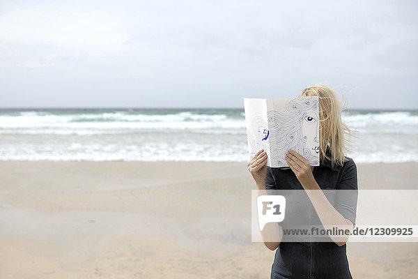 Frau bedeckt Gesicht mit Buch  liest Poesie am Strand