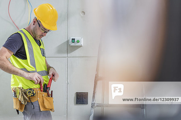 Electrician taking tools out of belt on construction site