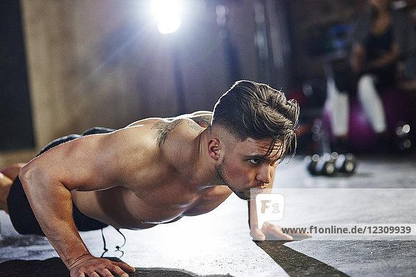 Ernsthafter Mann  der Liegestütze im Fitnessstudio macht.