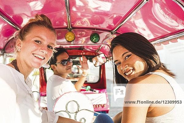 Thailand,  Bangkok,  Portrait von lächelnden Freunden beim Tuk-Tuk-Reiten
