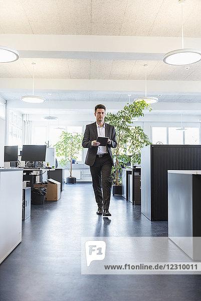 Geschäftsmann zu Fuß im Büro  mit digitalem Tablett